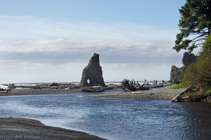Mouth of Cedar Creek at Ruby Beach where a rock with a window in it sits on the beach