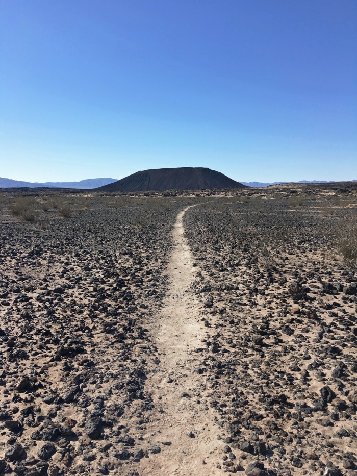Sandy trail through lava rock heading towards Amboy Crater in the distance