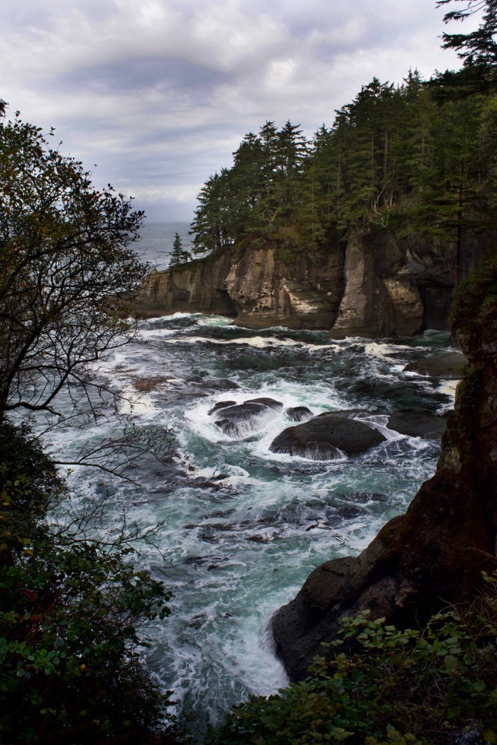 View from Cape Flattery of a coastal inlet surrounded by steep cliffs with waves crashing on the rocks below