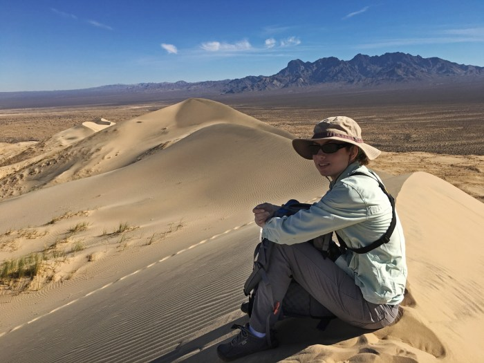 Christina sitting on the peak of Kelso Dunes with more dunes peaks in the distance and the desert mountains beyond