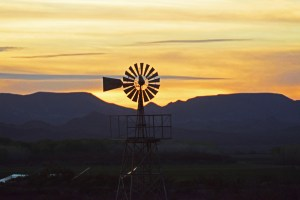 The silhouette of a windmill at Cibola NWR with the yellow sky and dark purple mountains in the background at sunset