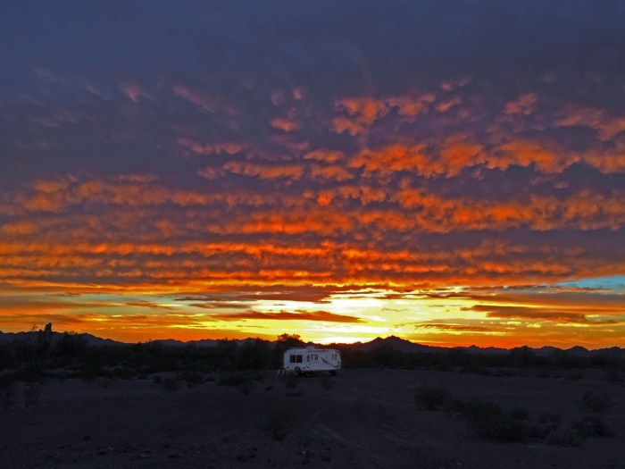 Dramatic sunset lighting up rafts of clouds in pinks, reds, and oranges, over our campsite at Kofa NWR
