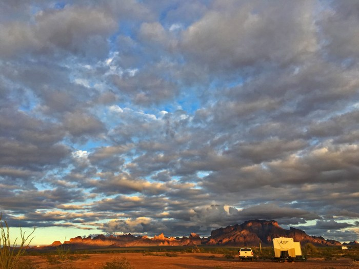 Our truck and trailer parked at Kofa NWR with the Kofa Mountains glowing orange in the sunset in the background and a sky full of clouds