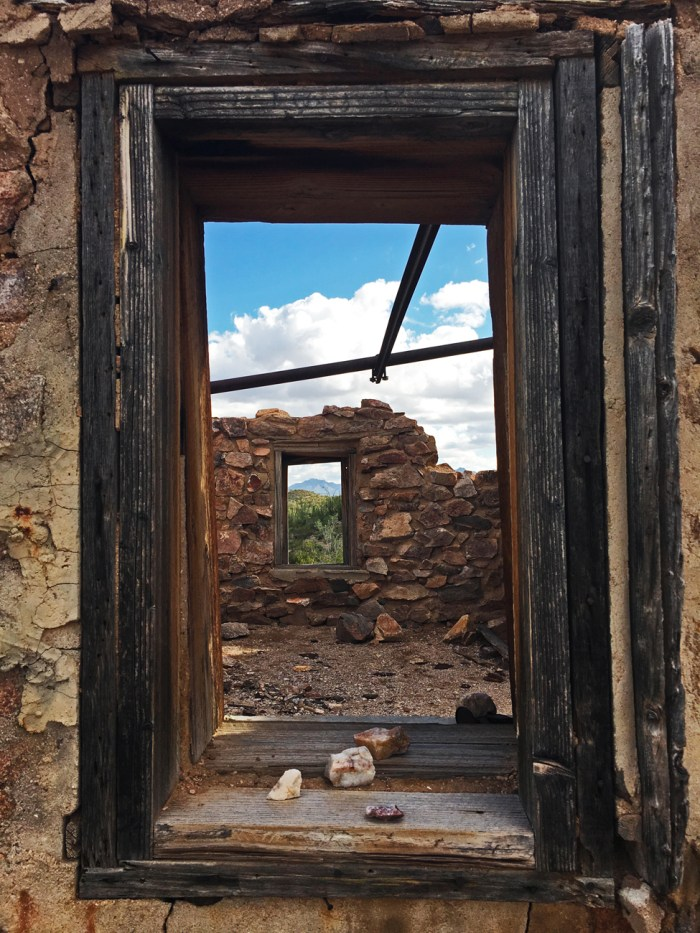 View through the window of an old stone structure to the window on the other side and the desert view beyond that window
