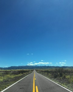 The two-lane road stretching out through the Arizona grasslands scattered with mesquite and mountains in the distance
