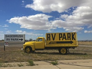 Sign on an old yellow truck for Sagebrush RV Park