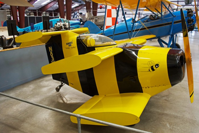 A tiny yellow and black striped airplane with unbelievably short wings