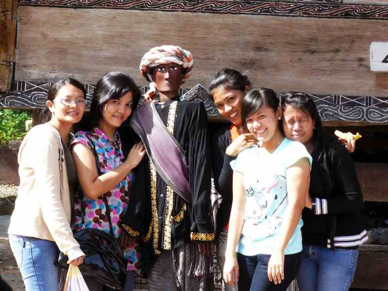 Local tourist posing for photo with Sigale Gale wooden puppet in Tomok village