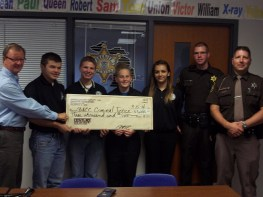 teacher, students and officers holding large check