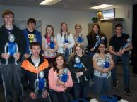 students posing with CPR training infants