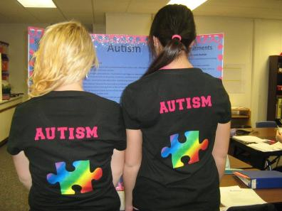 2 students wearing black shirts saying Autism with a puzzle piece