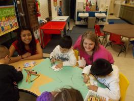 HS students helping preschoolers with art at table