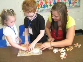 HS and Preschool students completing a puzzle