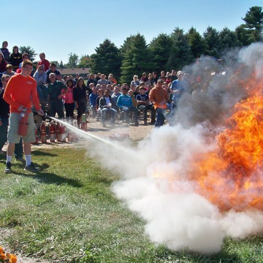 student putting out fire with extinguisher