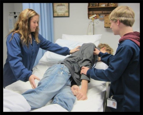 2 students practice rolling a patient over in bed