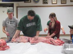 teacher and students processing a hog