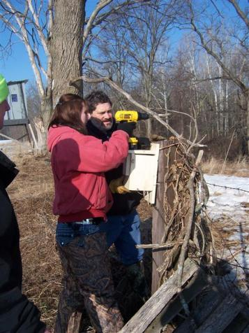 student and teacher mounting a bird house