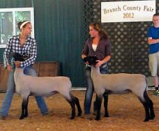 students posing with 2 lambs
