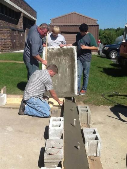 teacher and students pouring concrete