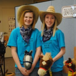 2 girls with cowboy hats and broom horses