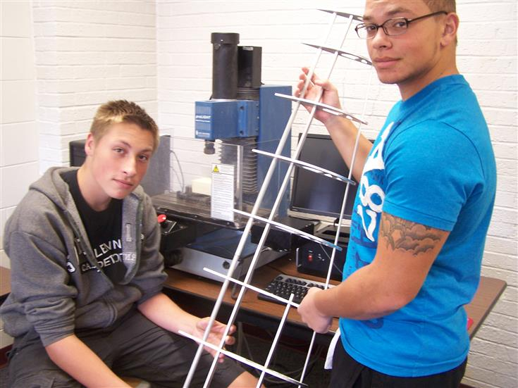 2 students holding a tower