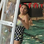 Gabby Stevens smiles as she climbs the rock wall located at the edge of the pool.