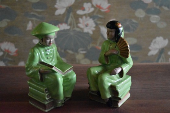 Ceramic Asian couple sitting on piles of books!