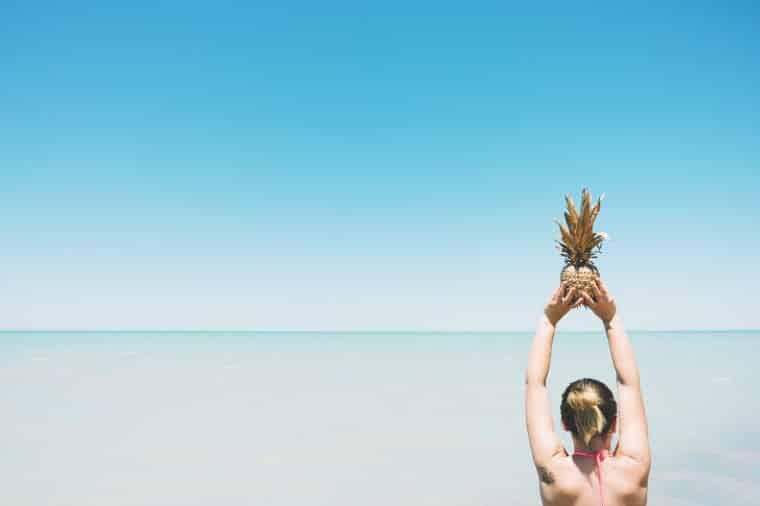 holding ananas above sea