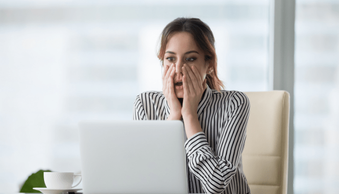 A woman feeling stressed looking at her computer
