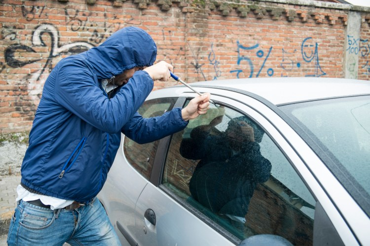 a hooded man tries to steal a car