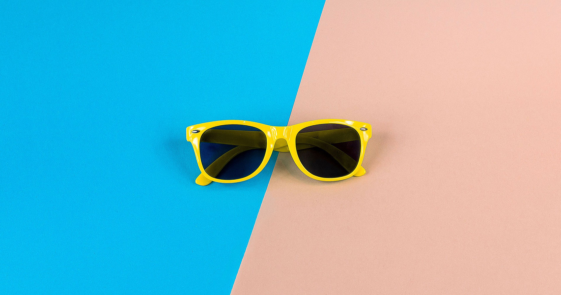 Yellow retro sunglasses on blue and pink background