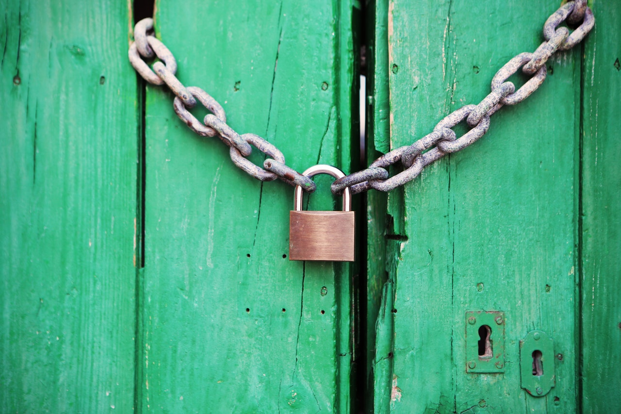 A green wooden door secured with a chain and padlock