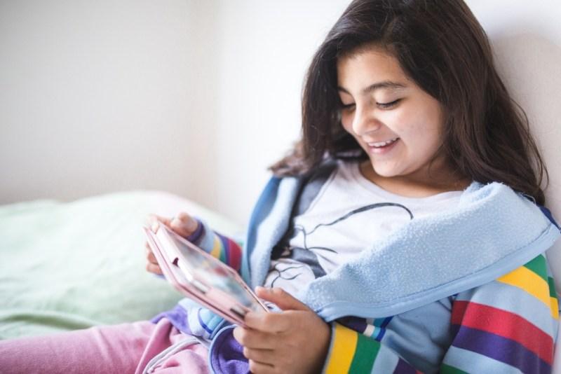 Menina bilíngue lendo no tablet.