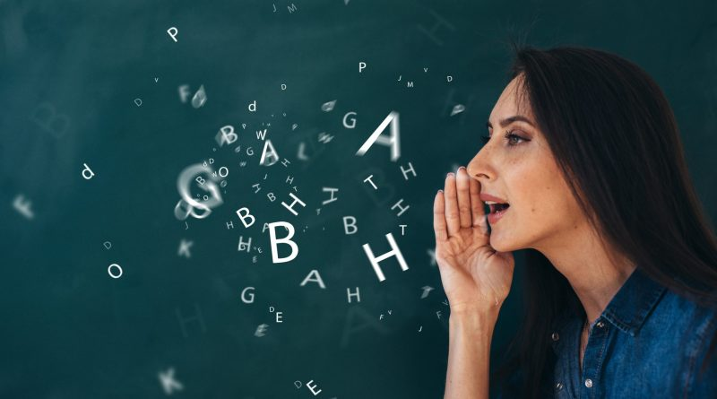 letras flutuando no quadro negro ao sair da boca de uma jovem