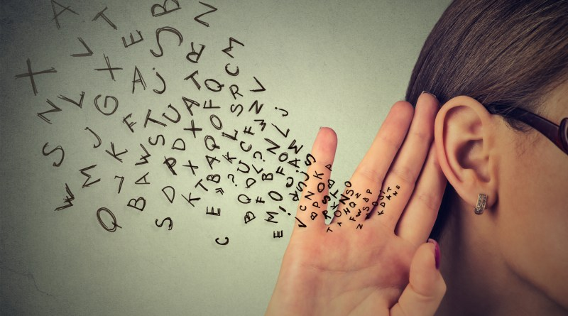 Mulher com letras do alfabeto em inglês saindo de seu ouvido.