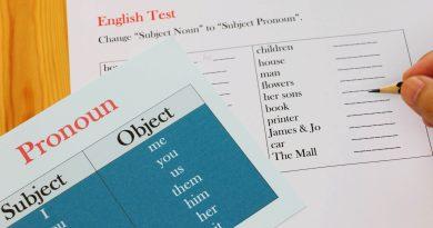 Folha com teste sobre pronomes em inglês sobre mesa de madeira.