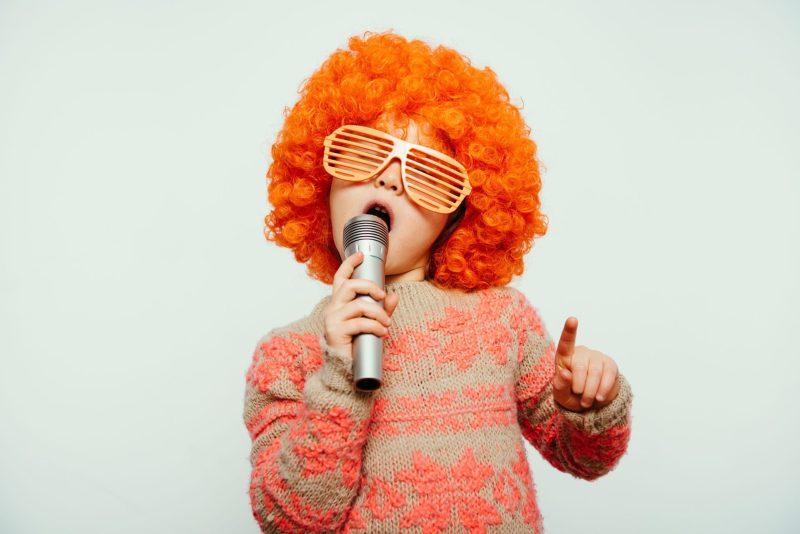 criança cantando canções populares em inglês