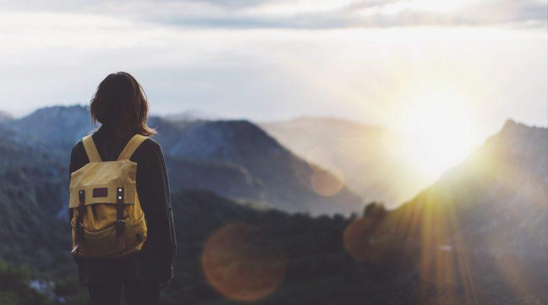 Mulher observando o sol e as montanhas ao horizonte.