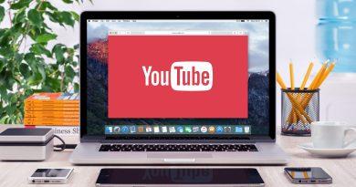 Computador em cima de uma mesa de madeira com canal do youtube aberto.