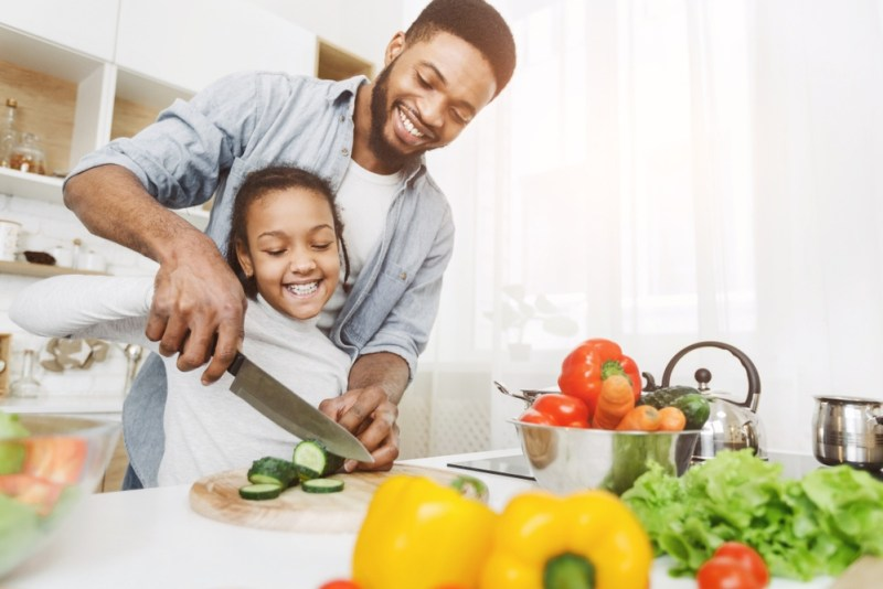 teaching his little daughter to cut vegetables.jpg