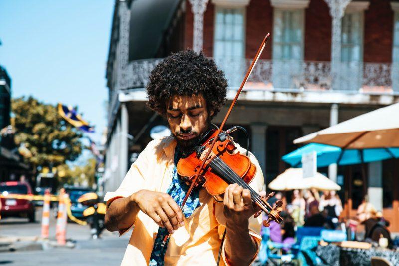 Homem negro tocando violino nas ruas da Irlanda.