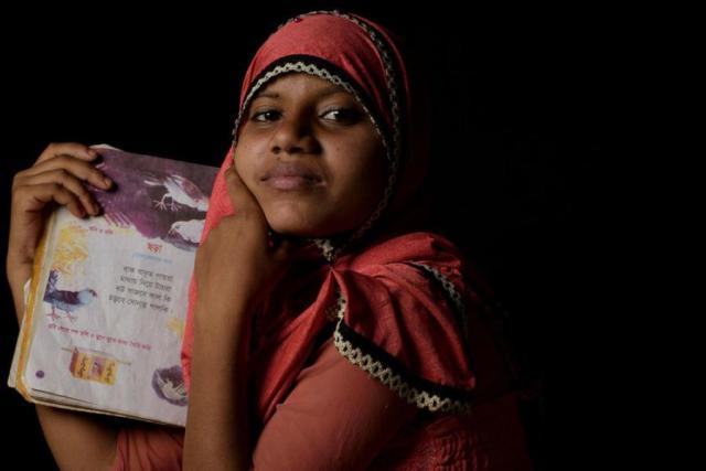 Uma refugiada Rohingya de quatorze anos mostra seu livro de poesia favorito em um campo de refugiados em Cox's Bazaar, Bangladesh.