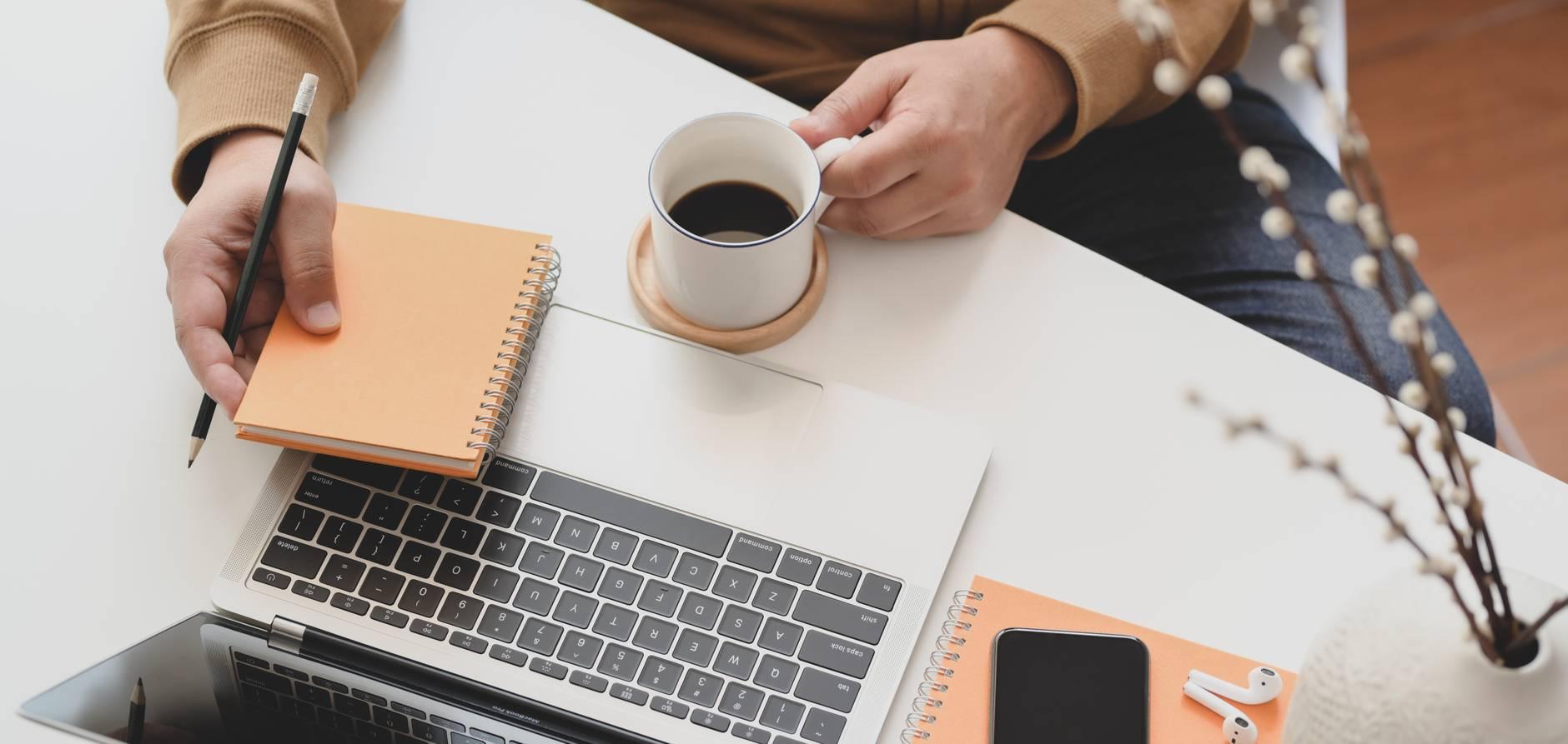 person holding white ceramic mug beside macbook pro