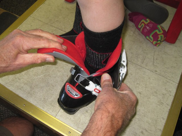 a child in a ski boot being checked to see if the boot fits.