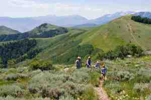 a family hiking through green meadows at deer valley resort