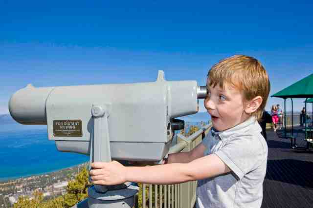 a young boy looking through a telescope from the top of heavenly resort over lake tahoe