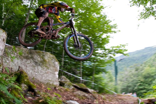 a downhill biker jumping over a large boulder in a downhill bike trail at snowshoe mountain resort in west Virginia