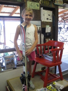 girl standing next to skis to see if they fit