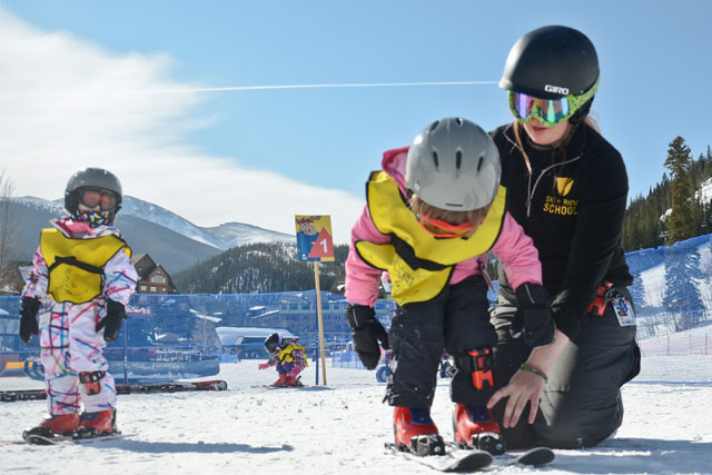 young children learning to ski with an instructor from the ski and ride school winter park