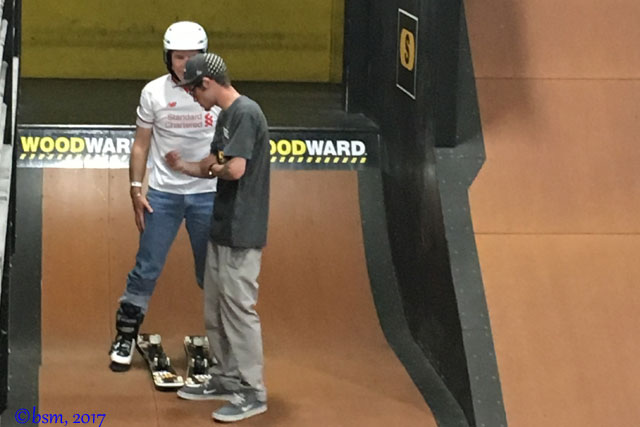 getting some coaching tips before skiing down a jump in the barn at woodward copper